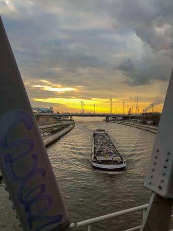 Large cargo ship transporting goods over the river under a colorful and dramatic sunset or sunrise sky as seen from a bridge with grafiti on it