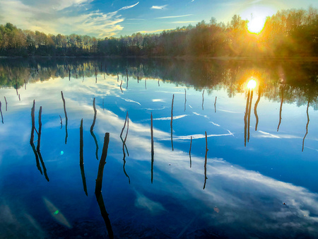 Tranquil idyllic landscape at a lake, with the vibrant blue sunset or sunrise sky, white clouds and green trees reflected in the clear blue water Stok Fotoğraf - 121842595