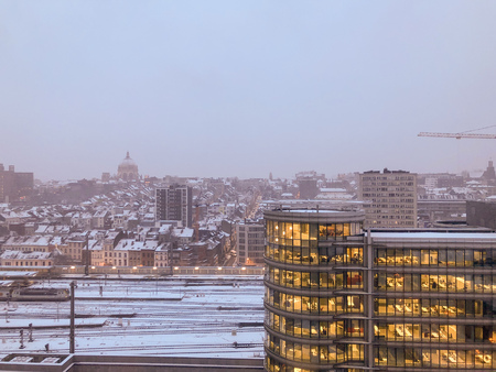 Grey and dramatic sunrise or sunset over the snow covered financial business district of the city of Brussels, Belgium, Europe. 写真素材
