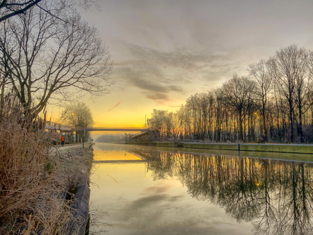 Dramatic and colorful sunrise or sunset over a beautiful landscape with a river or canal, treelined riverside and grass at sunrise creating a tranquile and quiet scenic nature background