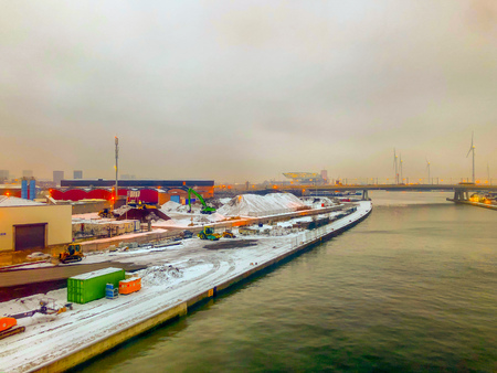 Antwerp, Belgium, February 2019: Industry and transport in the snow along the river Scheldt under a grey snowy sky
