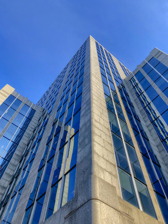 Details of the glass and concrete exterior of business office buildings skyline looking up with blue sky. Фото со стока
