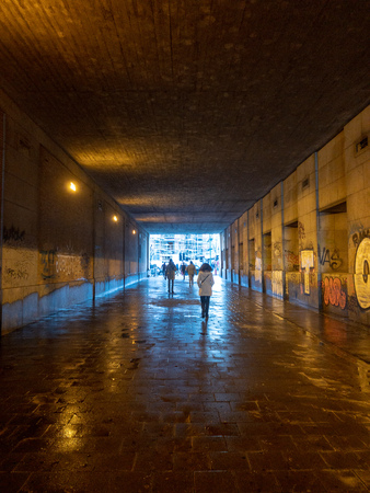 Silhouettes and their reflections of people walking in a tunnel in the city towards the light