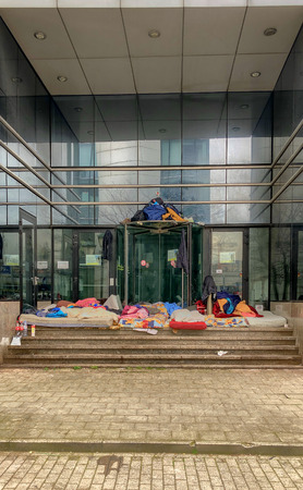 Homeless camps with sleeping bags and tents and tarp shelter in the entrance of an empty office building