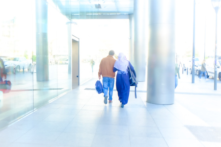 Rear view of an unrecognizable couple walking together with bags in a light city