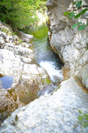 Water from a spring in the forests flowing down from the mountains in the Ardeche area in France Banco de Imagens - 124488015
