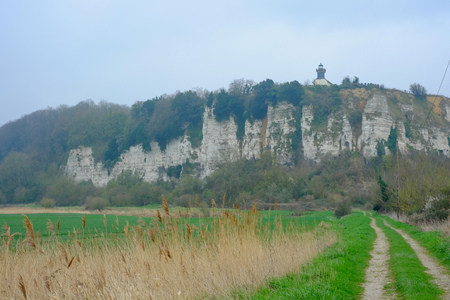 Path leading towards a chalk mountain with a lighthouse, Seine-Maritime, Normandy, France Stock Photo