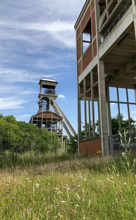 A disused coal mine pithead winding gear of an old Belgian coal mine shaft against a clear blue sky Banco de Imagens