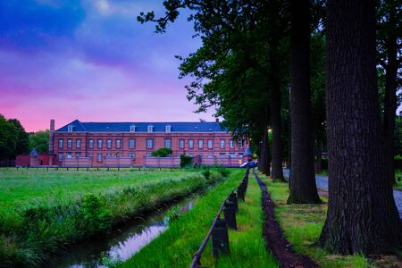Vintage prison building in Hoogstraten, Belgium showing the tree lined road towards the main building under a sunrise sky Фото со стока
