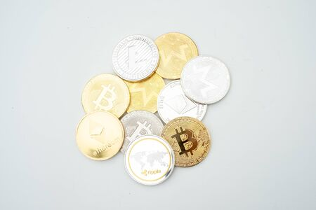 Bunch of Crypto currency coins with various of shiny silver and golden physical cryptocurrencies symbol coins, Bitcoin, Ethereum,. Litecoin, Monero, ripple with focus on BTC Bitcoin