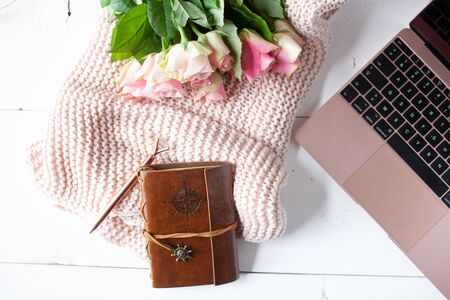 Womens workspace with laptop, bouquet of pink roses, a notebook, a pen and a cosy blanket in a flat lay top view