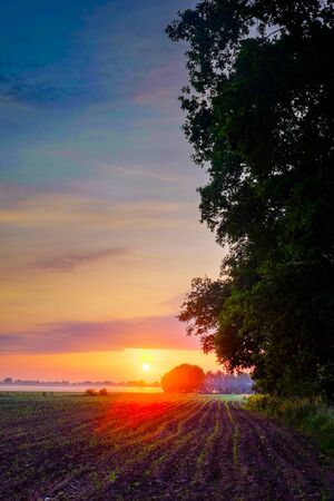 Colorful glowing sunrise over a countryside farming area, creating an idyllic scenic landscape