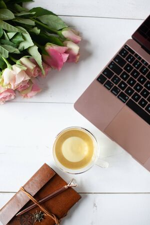 Womens workspace with laptop, bouquet of pink roses, a notebook, a pen and a cup of tea in a flat lay top view Stock Photo