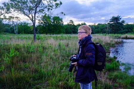 Young Photographer out in the open field Taking nature Photographs Outdoor With A Dslr Camera Stock Photo