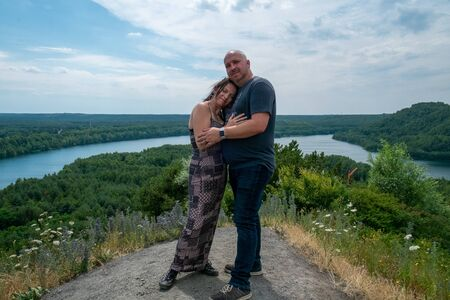 Loving couple of 30-40 years old outdoors hugging and standing tall on a hill with a river running through the woods the background