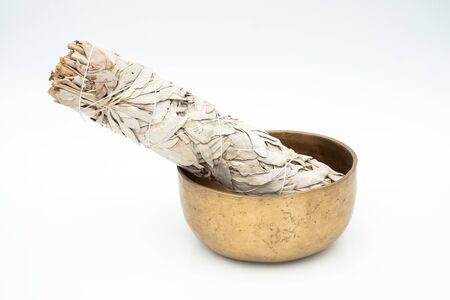 Composition à plat de sauge blanche séchée et d'anciens bols de méditation et de guérison tibétains traditionnels fabriqués à la main à partir de 7 métaux sacrés qui sont des accessoires typiques utilisés dans le bouddhisme, le yoga et la méditation Banque d'images