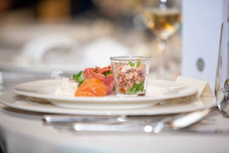 Tasty and colorful dinner plate with seafood such as salmon and shrimps in a restaurant or party setting