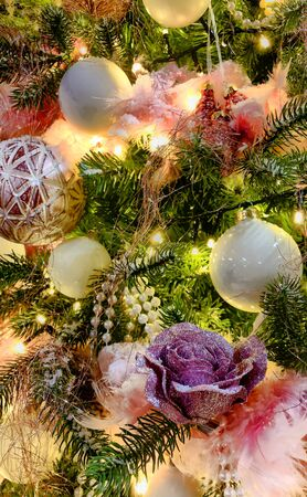 Close up of beautifully decorated Christmas ornament decorations in a Christmas tree with golden and white baubles and twinkling lights for the winter festive season