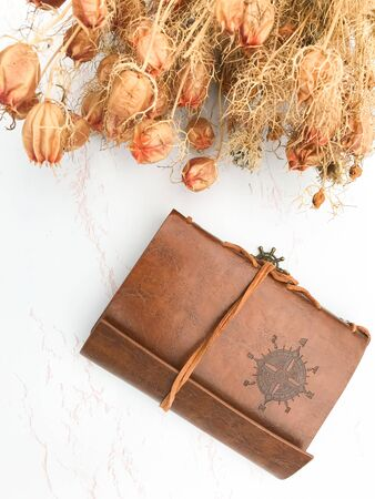 Dried flowers laying and a leather notebook laying on a white wooden background Фото со стока