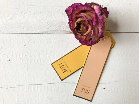 Close-up of love and gift tags next to a dried rose ready for the holidays