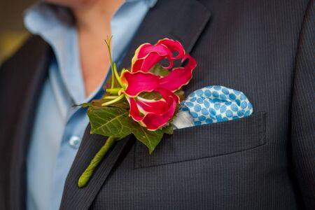 Bunte rosa Orchidee als Ansteckblume im dunklen Bräutigamanzug