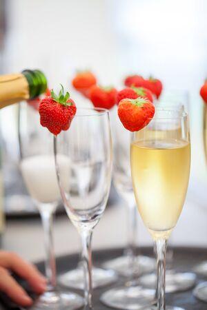Vino espumoso o champán y fresa sobre un fondo borroso que se vierte de la botella durante algún tipo de festividad o celebración, como una boda, cumpleaños o año nuevo. Foto de archivo