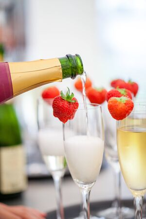 Sparkling wine or champagne and strawberry on a blurry background being poured out from the bottle during some sort of festivity or celebration such as a wedding, borthday or newyear Banque d'images
