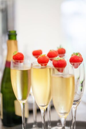 Glasses of sparkling wine or champagne and strawberry on a blurry background during some sort of festivity or celebration such as a wedding, borthday or newyear
