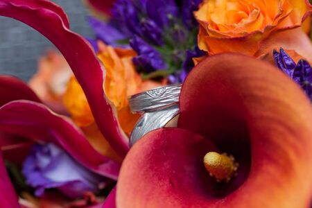 Close up with a colorful vivid mix of spring flowers of calas, zantedeschia, roses, orchids and more in orange, purple and pink