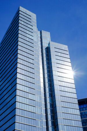 Low angle view of modern business buildings in city against blue clear sky Standard-Bild