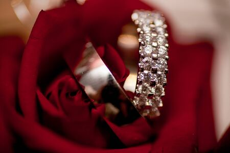Close-up of two Wedding rings and the wedding bouquet of red roses on a weddings day