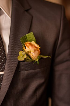 Soft Pink rose as a boutonniere in a Dark Groom Suit Banque d'images