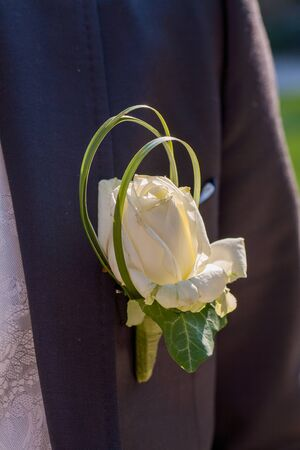 White rose as a boutonniere in a Dark Groom Suit