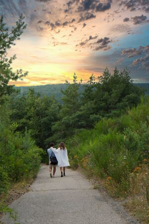 A loving couple walking down a dirt road in the forest under a dramatic sunset sky. High quality photo Stock Photo