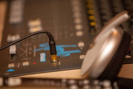Closeup of an audio mixing control panel, dj equipment, with headphones. Dj Music club life concept