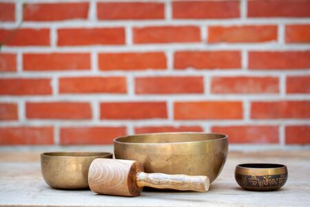 Ancient hand crafted traditional Tibetan meditation and healing singing bowls made from 7 sacred metals which are typical accessories used in buddhism, yoga and meditation, against a red brick wall