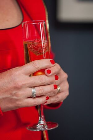 Unrecognizable gentle woman in red dress holding glass with champagne in her hands with stylish summer manicure. Female beauty and elegance.