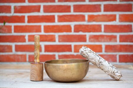 Dried white sage smudge stick and ancient hand crafted traditional Tibetan meditation and healing singing bowls made from 7 sacred metals which are typical accessories used in buddhism, yoga and meditation Standard-Bild