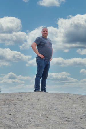 Forty something year old man standing tall on a hill with the blue sky and clouds in the background
