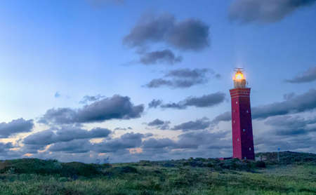 Lighthouse standing on the Dutch coast with a dramatic. and colorful dusk or dawn sky behind it. High quality photo