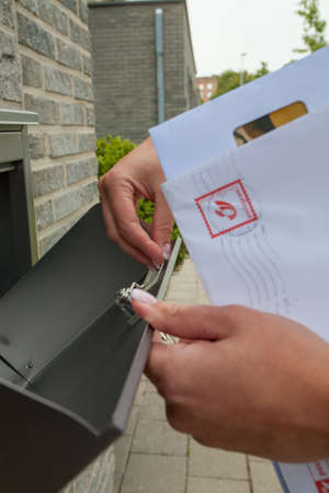 Close-up of womans hand holding envelope and inserting in or taking out of mailbox. High quality photo