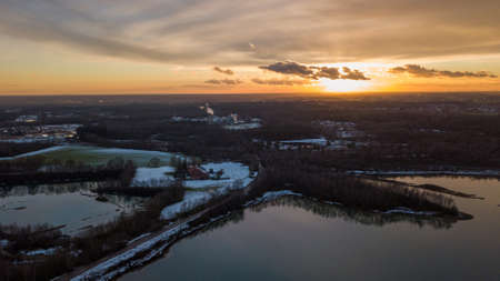 Aerial view of a beautiful and dramatic sunset over a forest lake reflected in the water, landscape drone shot. Blakheide, Beerse, Belgium. High quality photo