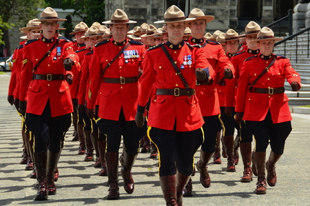 RCMP officers march in unison for a parade for fallen comrades.RCMP police marching in red uniforms.