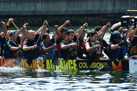Rowers rowing in the Dragon boat festival  in the inner harbor in Victoria BC.