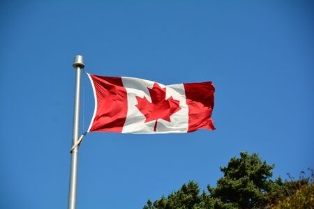 canadian flag: Canadian flag flies proudly in the skies.The maple leaf forever. Stock Photo