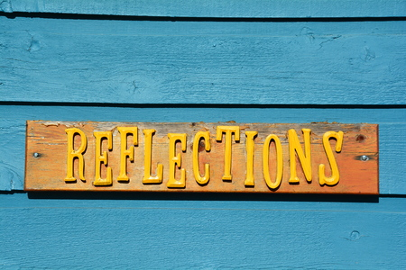 Wooden sign says REFLECTIONS on a blue background. Stok Fotoğraf