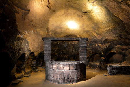 dimly: Ancient well inside the wine cellar in Montelpluciano Italy Stock Photo