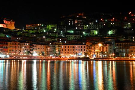 nightime: Rainbow on the water in Porto Santo Stefano Italy.