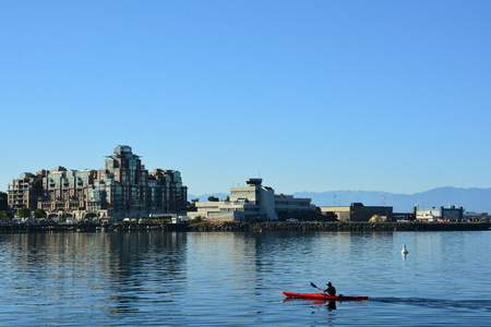 A kayaker paddles his way past high end real estate as he heads to the inner harbor in Victoria BC