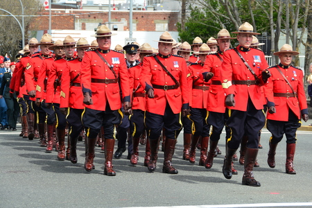 RCMP officers marching in red tunics to the church